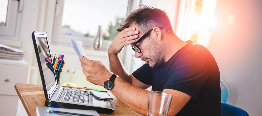 Man sitting in home office, reading letter and felling worried. With one hand holding letter and with other hes forehead