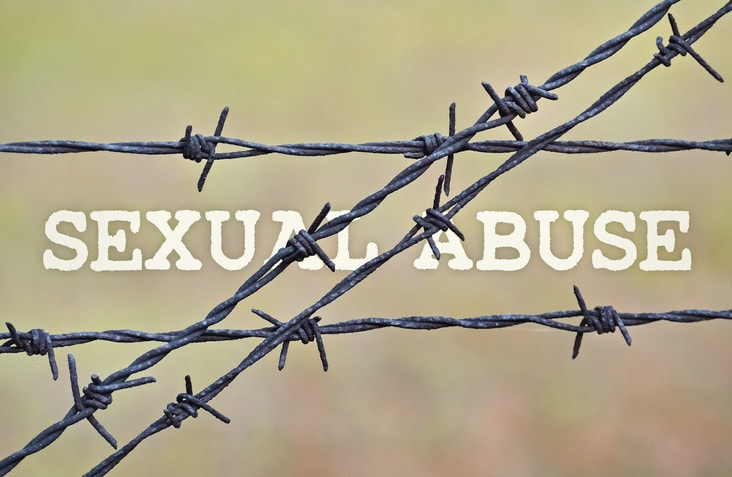 Text Sexual Abuse written under a wire fence