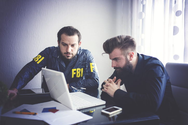 Two agents working in office looking at sex offender registration