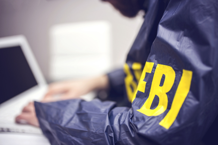 FBI agent working on his computer in office investigating child pornography