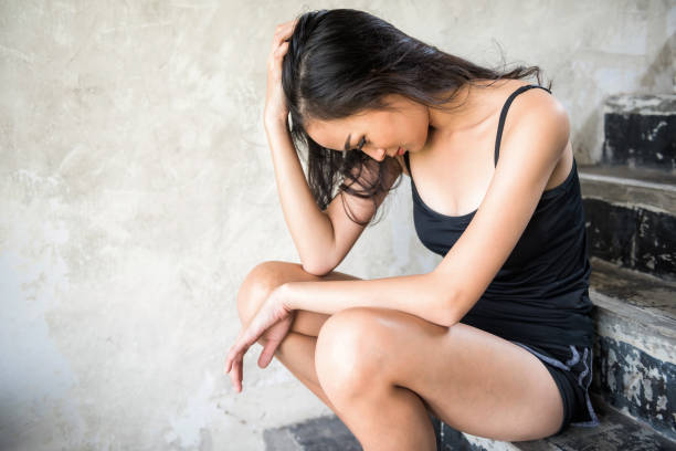 Depressed prostitute Asian woman sit on staircase. harlot girl suffered from sex abuse in abandon brothel room. Sexual harassment or rape. Social issue for poor people.