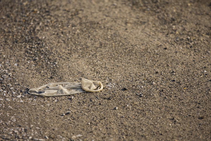 A discarded condom in a beach parking lot.