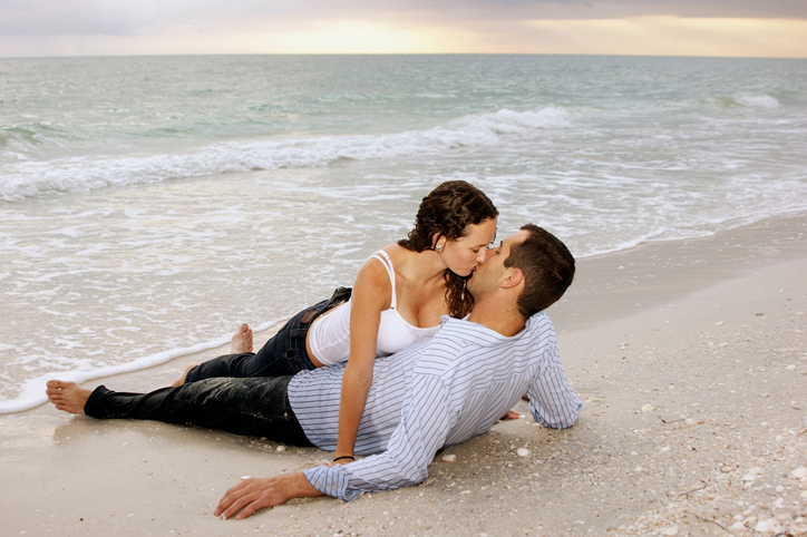 young adult couple kissing at the beach as the sun sets.