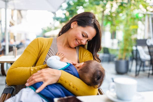 Young mother breastfeeding her baby boy in public while sitting in a cafe