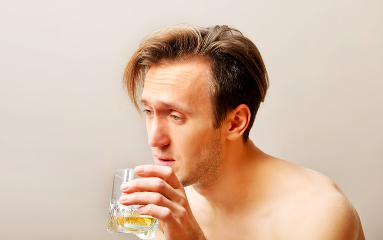 Drunk man sitting on bed and drinking whiskey.